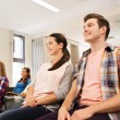 Group of smiling students in lecture hall — Stock Photo #58907393