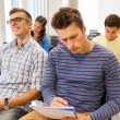 Group of smiling students in lecture hall — Stock Photo #58907595