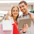 Couple with tablet pc and shopping bags in mall — Stock Photo #58907737