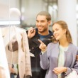 Happy young couple with shopping bags in mall — Stock Photo #58907971