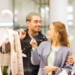 Happy young couple with shopping bags in mall — Stock Photo #58907979