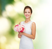 Smiling woman in white dress with bouquet of roses — Stock Photo