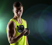 Young man with dumbbell flexing biceps — Foto de Stock