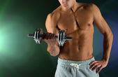 Close up of young man with dumbbell flexing biceps — Stock Photo