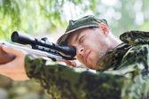 молодой солдат или охотник с оружием в лесу — Стоковое фото