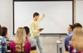 Group of smiling students and teacher in classroom — Stock Photo