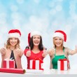 Smiling women in santa helper hats packing gifts — Stock Photo #58948231