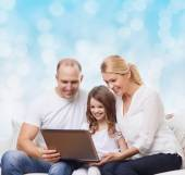 Smiling family with laptop — Stock Photo