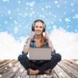 Happy young woman with laptop and headphones — Stock Photo #58975237