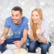Smiling couple watching tv at home — Stock Photo #58975847