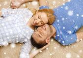 Happy couple lying on floor head to head at home — Stock Photo