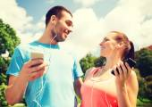 Two smiling people with smartphones outdoors — Stock Photo