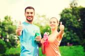 Smiling couple with bottles of water outdoors — Stock Photo