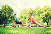 Smiling couple stretching outdoors — Stok fotoğraf