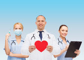 Group of smiling doctors with red heart shape — Stock Photo