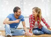 Smiling couple measuring wood flooring — Stock Photo