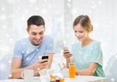 Smiling couple with smartphones having breakfast — Stock Photo