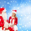 Smiling little girl with santa claus and gifts — Stock Photo #59047071