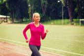 Smiling woman running on track outdoors — Stock Photo