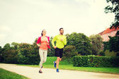 Smiling couple running outdoors — Stock Photo