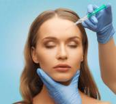 Beautiful woman face and hands with syringe — Stock Photo