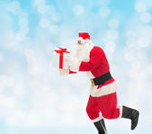 Man in costume of santa claus with gift box — Stockfoto
