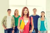 Smiling students with teenage girl in front — Stock Photo