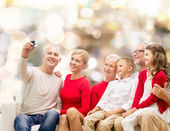 Smiling family with camera — Stock Photo