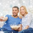 Smiling couple watching tv at home — Stock Photo #59097053