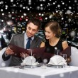 Smiling couple with menus at restaurant — Stock Photo #59097923