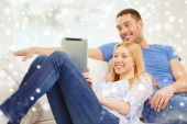 Smiling happy couple with tablet pc at home — Stockfoto