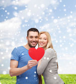 Happy couple with red heart shape hugging outdoors — Stock Photo