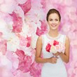 Smiling woman in white dress with bouquet of roses — Stock Photo #59103819
