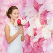 Smiling woman in white dress with bouquet of roses — Stock Photo #59103823