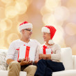 Happy senior couple in santa hats with gift boxes — Stock Photo #59104073