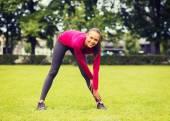 Glimlachend zwarte vrouw die zich uitstrekt been buitenshuis — Stockfoto