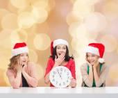 Smiling women in santa helper hats with clock — Stock Photo