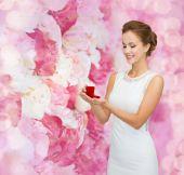 улыбающиеся женщина, держащая красная подарочная коробка с кольцом — Стоковое фото