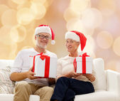 Happy senior couple in santa hats with gift boxes — Stock Photo