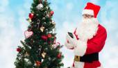 Santa claus with smartphone and christmas tree — Stock Photo