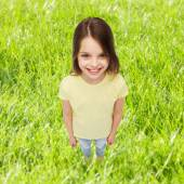 Smiling little girl over green grass background — Foto Stock