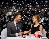 Smiling couple with red gift box at restaurant — Stock Photo