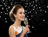 Leende kvinna anläggning glas mousserande vin — Stockfoto