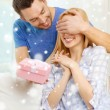 Smiling man surprises his girlfriend with present — Stock Photo #59311081