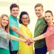 Smiling students with hands on top of each other — Stock Photo #59312303