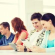 Smiling students with tablet pc at school — Stock Photo #59314349