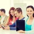 Smiling students with tablet pc at school — Stock Photo #59314395