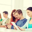Smiling students with tablet pc at school — Stock Photo #59314403