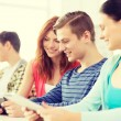 Smiling students with tablet pc at school — Stock Photo #59314425