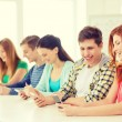 Smiling students with smartphones at school — Stock Photo #59314561